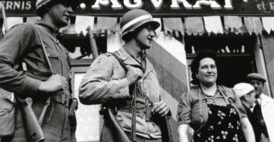 """A black and white photo of soldiers standing next to a woman with a sign in the background that reads """"Vive L'Amerique"""""""