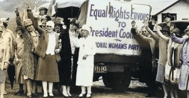 A group of women standing in front of a sign that reads Equal Rights Envous to President Coolidge -- National Woman's Party